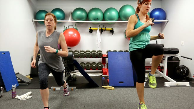 Alison Yano, of Pleasant Ridge, left, and Katie Bird, of Norwood, take a boot camp class at Cincinnati Fit Body Bootcamp in Deer Park on Friday, Jan. 2, 2015. Both regularly work out and were taking part in a challenge Friday morning: Anyone who took four classes Friday was eligible for a free month of boot camp. This was Session No. 3.