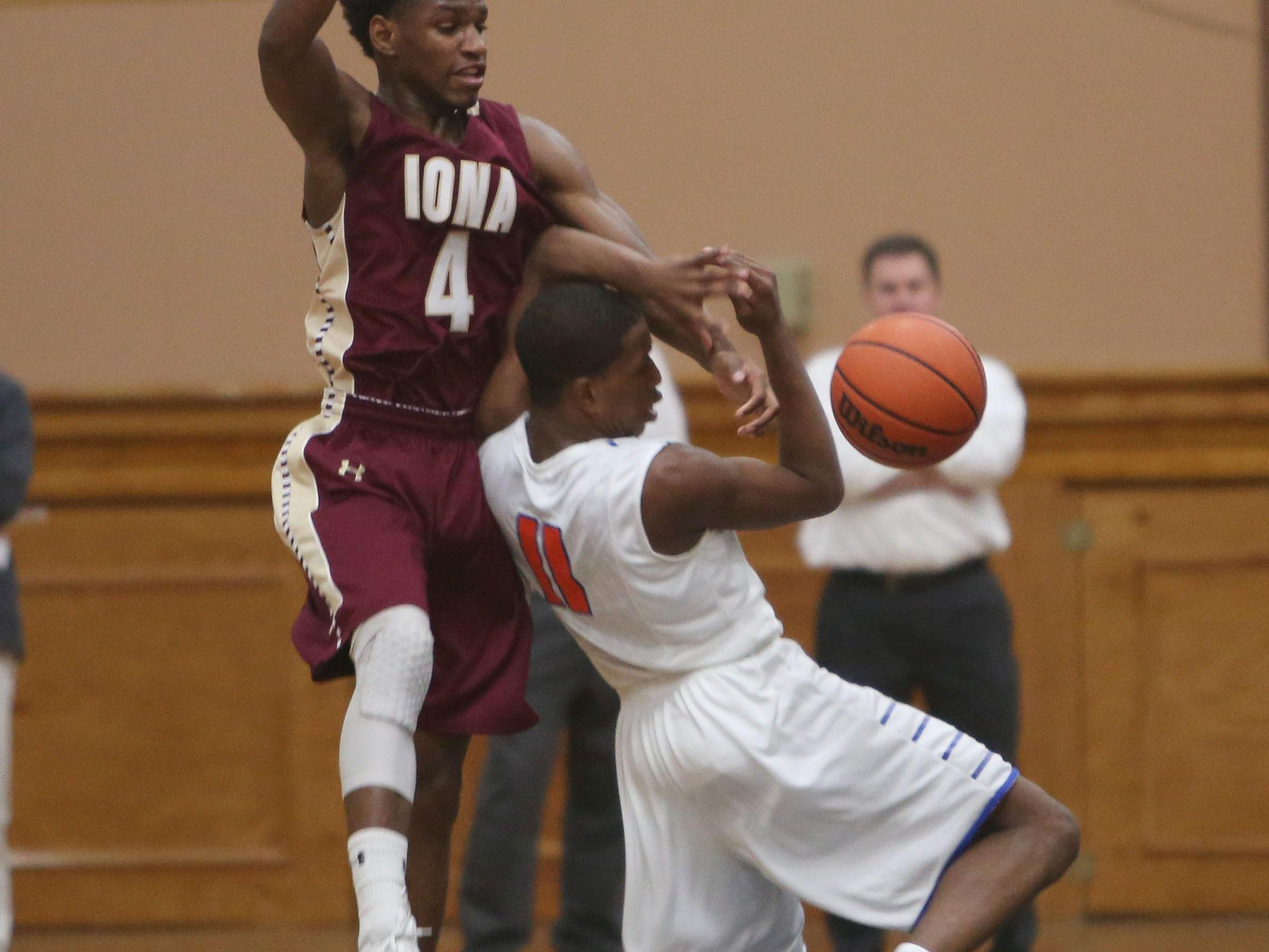 Iona's Gio Gabbidon (4) knocks the ball away from Saint Raymond's Isaiah Washington (11) during the CHSAA Archdiocesan tournament semifinal at Mount Saint Michael Academy in the Bronx Feb. 23, 2016. Saint Raymond won the game 55-47.