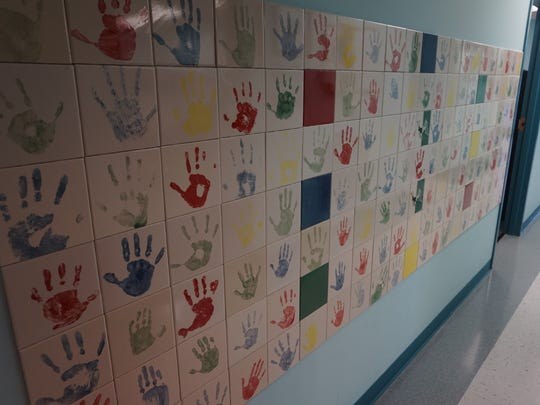 Wall of hand prints of child sex abuse victims at the