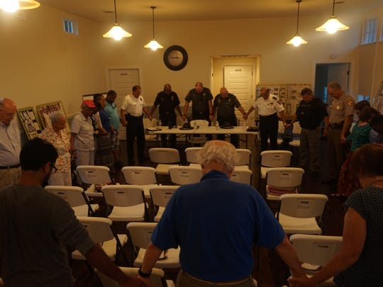 Police and attendees hold hands in prayer following a July 21 NAACP meeting.