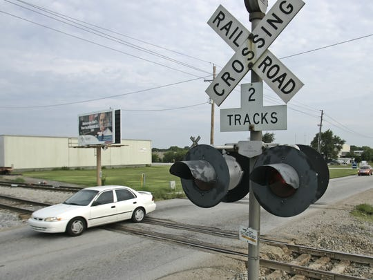 Traffic passes over the railroad crossing on Concord