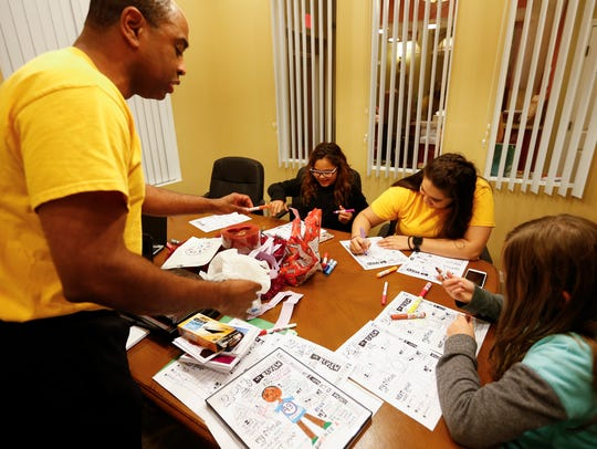 Volunteer Lawrence Anderson leads an activity during a Ujima program meeting at the Bartley-Decatur Neighborhood Center on Wednesday, Dec. 13, 2017.