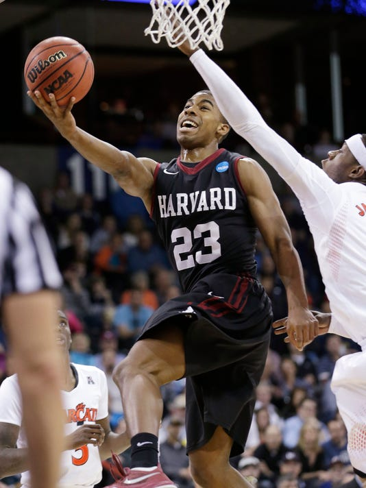 Harvard's Wesley Saunders (23) drives the last past Cincinnati's Justin Jackson in the second half during the second round of the NCAA college basketball tournament in Spokane, Wash., Thursday, March 20, 2014. Harvard won 61-57. (AP Photo/Elaine Thompson)