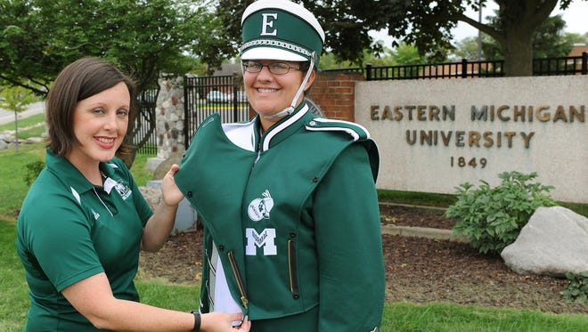 In this September 2012 file photo provided by Eastern Michigan University, Amy Knopps, left marching band director, shows off the Huron and Normalite logos imbedded in the schools' new marching band uniforms that is worn by uniform manager Maria Eloff.