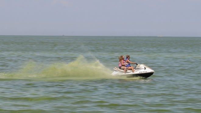 Jet-skiers churn up toxic blue-green algae on Lake Erie in Port Clinton in the summer of 2015, the worst year on record.