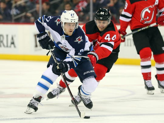 Winnipeg Jets left wing Nikolaj Ehlers (27) skates with the puck while being defended by New Jersey Devils left wing Miles Wood (44) during the first period at Prudential Center in Newark on March 8, 2018.