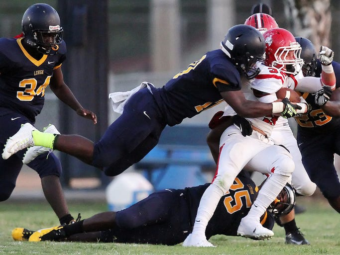 Lehigh High School defenders Yovani Tomas-Cabrera, top, and Chris Matheus, bottom, tackle North Fort Myers' ST. Amand on Friday at Lehigh High School.