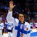 Finland's Teemu Selanne waves as he celebrates with his bronze medal after defeating Team USA in their men's ice hockey bronze medal game on Saturday.