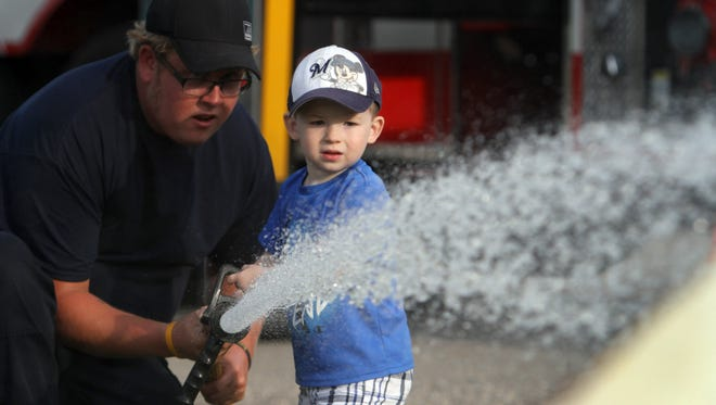 Firefighter Matt Schmeling helps 2<AF>1/2<XA>-year-old Jack Weber man the fire hose during a past National Night Out in Sussex. This year's event is Wednesday, Aug. 8, at the Sussex Civic Center.