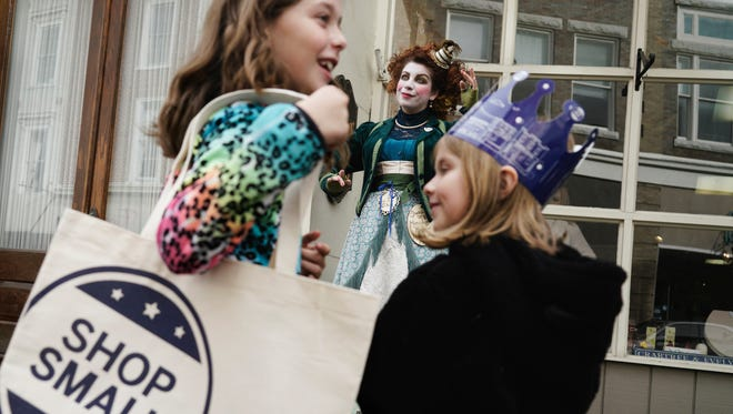 Carmel Clavin, center, Director/Producer of Spectacle & Mirth, performs for young shoppers Sydney Herz, 9, left, and her sister Camryn Herz, 7, during the Small Business Saturday event in downtown Staunton on Nov. 28, 2015.
