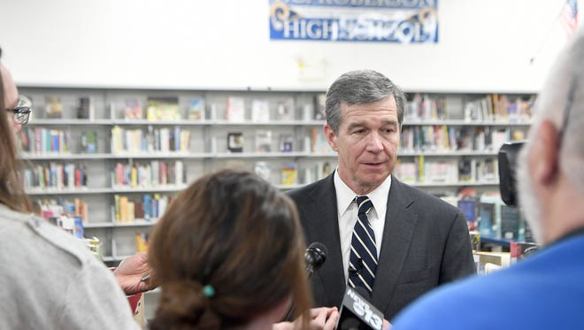 Governor Roy Cooper talks with members of the media following a tour of Roberson High School on Monday, April 23, 2018. Cooper announced that his new budget will include increased funds for school safety from several angles.