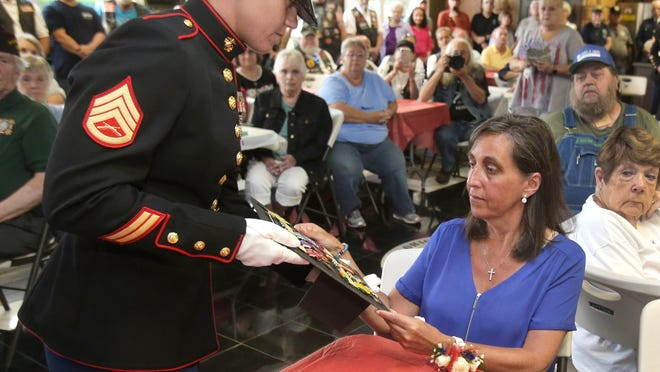 Marine Staff Sgt. Victoria Poland presents the war medals of Ronald Poland, who was killed in action in Vietnam 50 years ago, to her second cousin, Tina M. Hoffman, Poland's daughter, who was only 3 years old when her father died. The presentation was made a little more than a year ago at the Ohio Veterans' Memorial Park in Clinton.