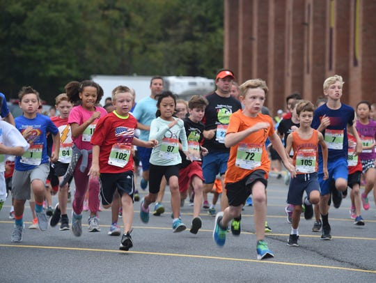 A pack of kids' mile runners sprint toward the finish