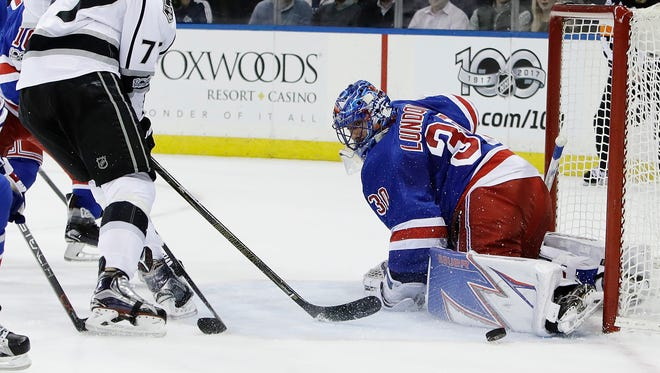 New York Rangers' Henrik Lundqvist (30), of Sweden, stops a shot on the goal by Los Angeles Kings' Jeff Carter (77) during Monday's game.