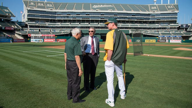 Athletics owner Lew Wolff (left), MLB commissioner Bud Selig (center), and Athletics manager Bob Melvin (right) talk on the field before a game in August.