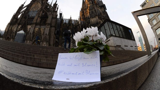 "Flowers and a letter reading ""One doesn't beat women - not even with flowers"" are laid down in front of Cologne's landmark, the Cologne Cathedral, near the main railway station, on January 7, 2016, to commemorate victims of the apparently coordinated sex attacks in the western city during New Year's Eve."