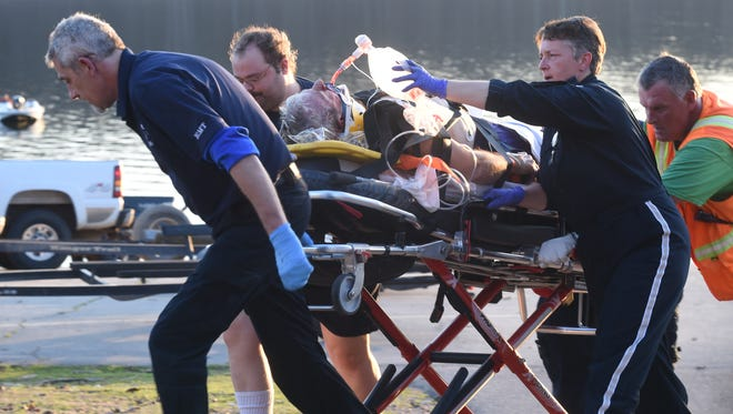 An Air Evac flight crew along with other emergency personnel wheel a victim to a waiting helicopter at Fout's Boat Dock on Norfork Lake early Thursday night following a boating accident.