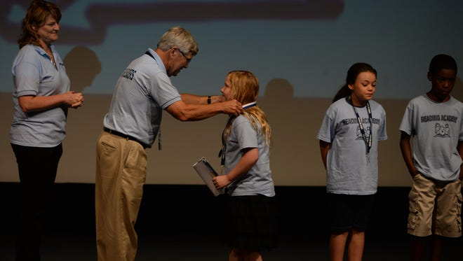 "Students who attended Third Grade Academy receive medals from chairman Rick Ahaus in July 2015 during the academy's closing celebration at Civic Hall.  The children's T-shirts say ""Readers are Leaders."""
