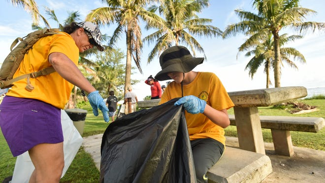 In this Sept. 17, 2016, file photo, Cole Zmijski, 9, sorts through a garbage bag during the International Coastal Cleanup at the War in the Pacific National Historical Park in Asan.