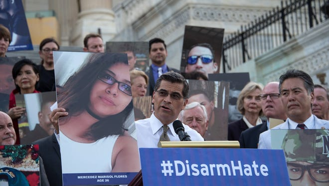 Xavier Becerra, a Democratic U.S. Representative from California, speaks as members and supporters of the U.S. Congressional LGBT Equality Caucus, including Rep. Mark Takano (right), hold photos of victims of the Pulse nightclub attack during a vigil in July in Washington, D.C.
