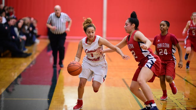 Livonia Churchill's Shae Smith (1) dribbles down the sideline past Westland John Glenn defenders Jasmine Edwards (32) and Dominique Stribling (24) during Friday's district final.