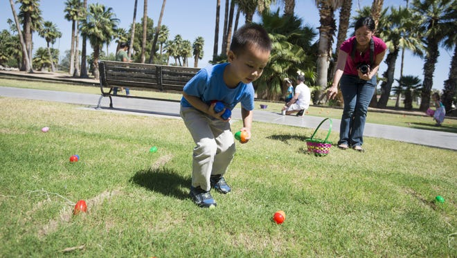 Children collect Easter eggs during a free Easter-egg hunt for children at the Enchanted Island theme park in Phoenix on Saturday, April 15, 2017.