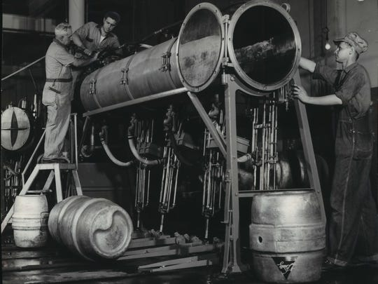 Workers make ready a keg-filling line at Blatz Brewing