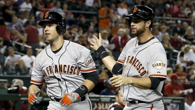 San Francisco Giants' Buster Posey, left, gets a slap on the back from teammate Brandon Belt after Posey hit a two-run home run against the Arizona Diamondbacks during the ninth inning of an opening day baseball game, Monday, March 31, 2014, in Phoenix.  The Giants defeated the Diamondbacks 9-8.