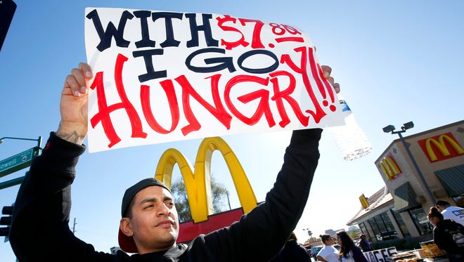 Alex Robles joins dozens of sign-holding protesters at a rally against low wages for fast-food workers in front of a McDonald's on Dec. 5 in Phoenix.