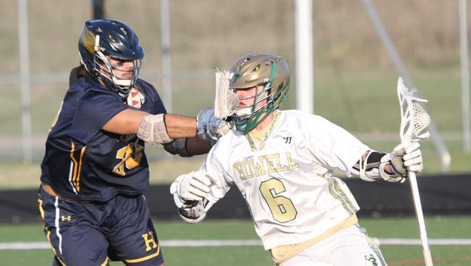 Hartland's Jack Callaghan (left) defends Howell's Jack Radzville during the Eagles' 18-2 lacrosse victory on Monday, April 30, 2018.