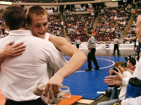 Bermudian Springs assistant wrestling coach Trevor Byers, left, gives Derek Schmelyun (brother of Rickey Schmelyun) a hug after Schmelyun won his third-place match at the PIAA Class AA championships last season at Giant Center.  - DAILY RECORD / SUNDAY NEWS - KATE PENN