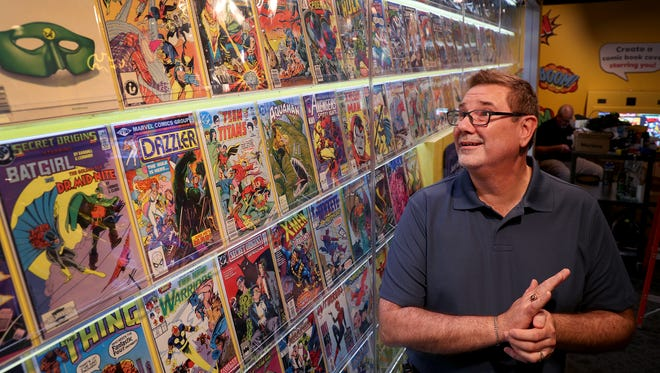 "Chris Carron, director of collections at the Children's Museum of Indianapolis, looks at a wall of comic books at the new ""American Pop"" exhibit."