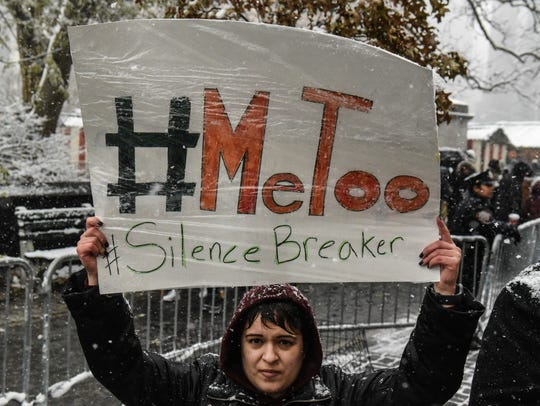 People carry signs addressing the issue of sexual harassment