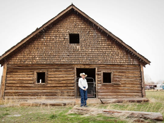 Kelly Flynn stands in front of one of his barns in
