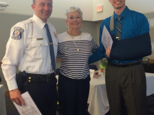 Pat Hill (center) poses with Commander Justin DuLong and PSO Matt Miracle, who helped save her life last year.