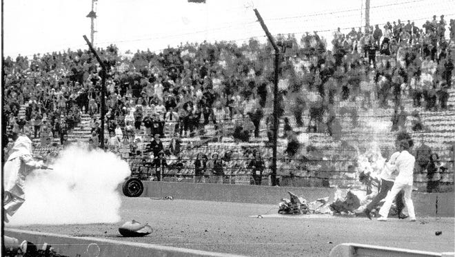 Track safety and rescue crew members deal with hot fuel vapors from the torn remains of a crashed race car near the first turn as a result from the Salt Walther car that was demolished during the start of the 73 Indianapolis 500.