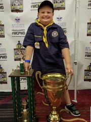 Garrett Kendrick of Fort Loudon shows off his pro-stock trophies from the World Championship Pinewood Derby.
