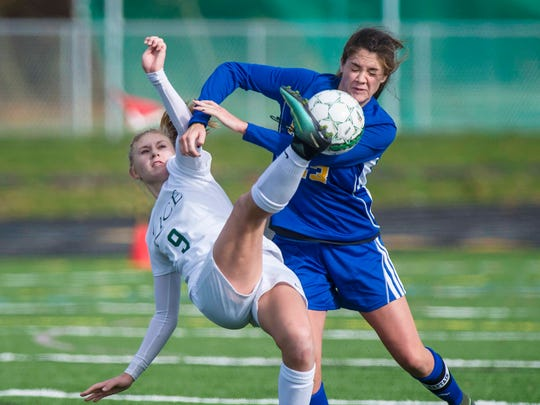 Rice Memorial's Alex Dostie, left, kicks the ball in front of Milton's Brooke Caragher during the girls Division 2 high school state championships in South Burlington on Saturday, November 4, 2017.