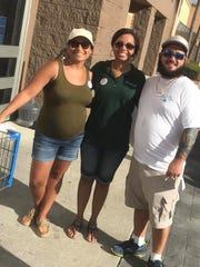 From left, Melanie Baculima, Cherelle Mansfield and Chris Kranker help spread the word about Stuff the Bus to visiting Wal-Mart shoppers.