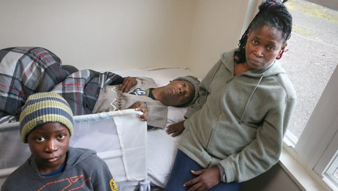 Charlotte Gosso, with her sons Ephraim, 10, and Guy, 22, in the apartment they live in in Rochester Friday, Jan. 27, 2017.  The family emigrated here from C™ote d'Ivoire.  Guy is also bed ridden.
