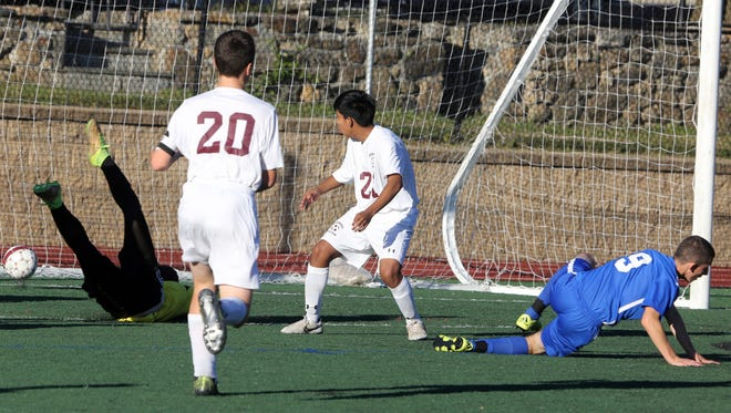 Ossining goal keeper Luke DeAngelis tumbles after failing to stop a shot by Port Chester's Francisco Romero for the first goal of the game during a varsity soccer game at Ossining High School Oct. 14, 2016.