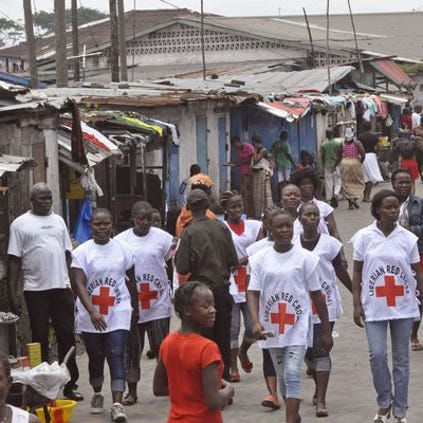 Red Cross workers walk through a section of West Point, an area that has been hit hard by the Ebola virus, with residents not allowed to leave as government forces clamp down on movement to prevent the spread of Ebola, in Monrovia, Liberia, on Aug. 27, 2014.