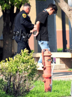 In this Monday, Aug. 28, 2017 photo, police take a man into custody after a shooting at a public library in the eastern New Mexico community of Clovis. Authorities on Tuesday identified the gunman accused of opening fire inside the library as a Nathaniel Jouett, 16-year-old high school student who they say killed a youth librarian and a second employee while wounding four others. The Associated Press generally does not identify juveniles accused of crimes, but is identifying Jouett because of the seriousness of the crime and because authorities said they plan to file a motion requesting the case's transfer from the juvenile system to adult court.