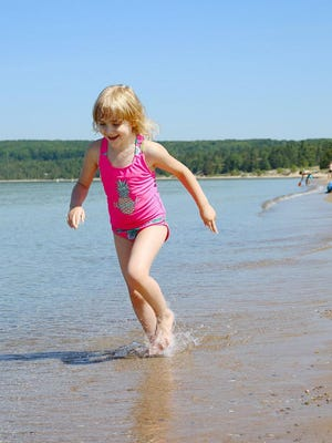Onya Hoffman plays on the beach at Petoskey State Park with her mother in mid-June.