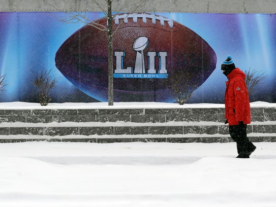 Snow falls as a man passes signage for the NFL Super