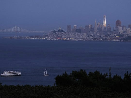 In this photo taken Saturday, July 22, 2107, the setting sun is reflected on the Salesforce Tower in the San Francisco skyline in this view from Sausalito, Calif.