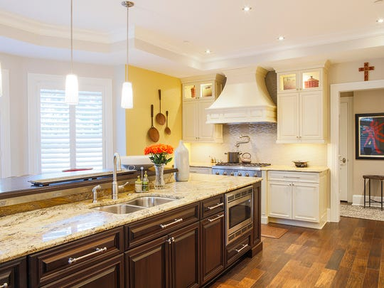 he kitchen features mahogany cabinets under the granite island and maple cabinets with a feathered cream glaze around the perimeter.
