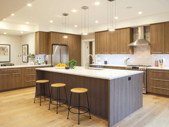 For a consistent look, engineered eight-inch-wide plank, oil-finished oak in a gray wash is used throughout the main level. The laminate cabinets were custom-made. The island, featuring a Blanco Silgranit sink, is topped by quartz.