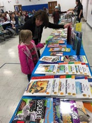 Students at the Durban Avenue School check out books during Family Book Bingo Night.