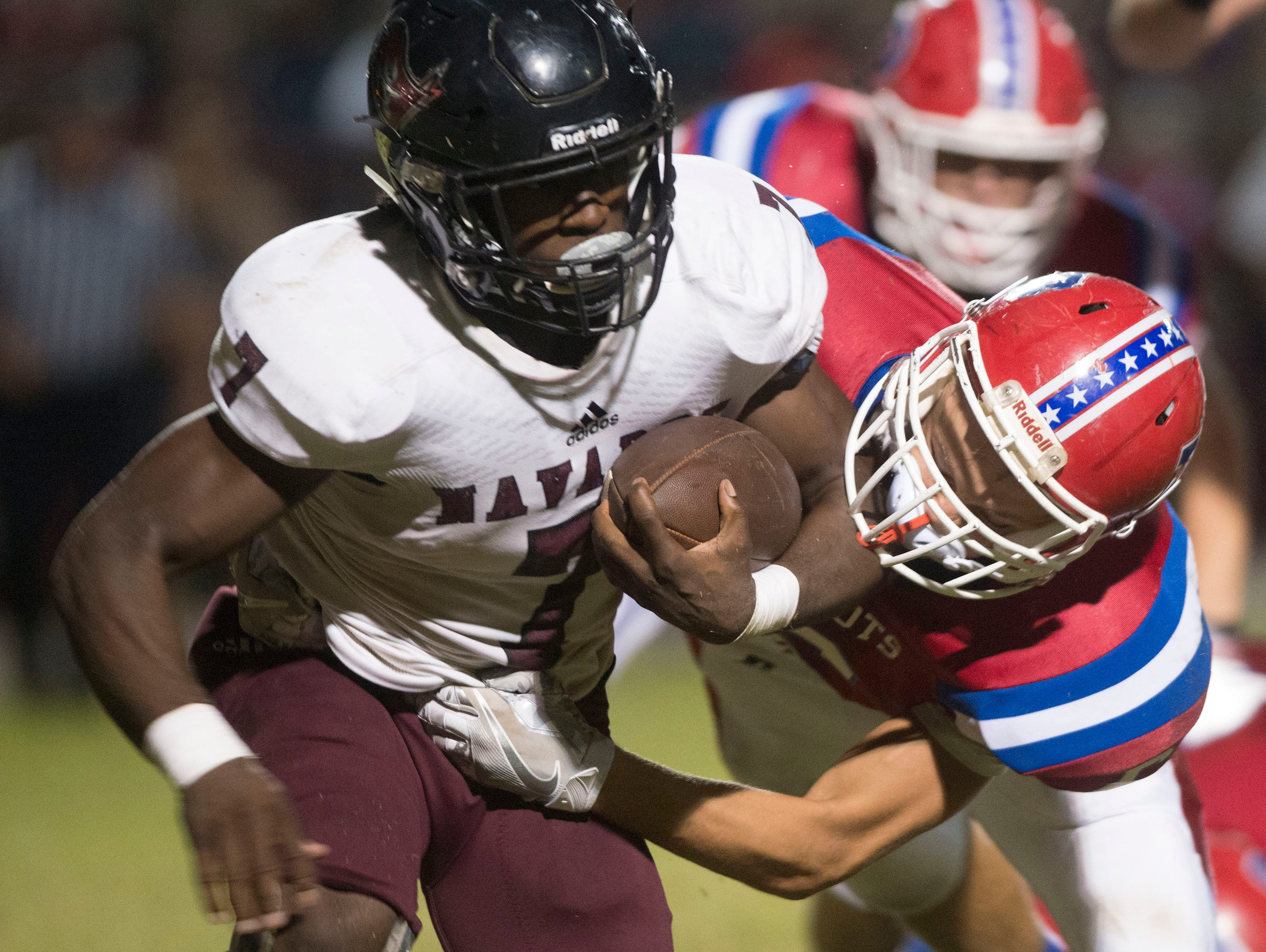 Navarre High School star running back Michael Carter (No. 7) gets wrapped up behind the line of scrimmage by the Pace High School defense during the District 2-6A matchup Friday night.